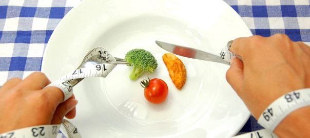 1 piece of broccoli and 1 cherry tomato on a plate being eaten with a knife and fork bound with tape measure